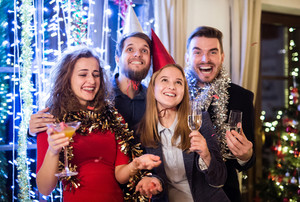 Group of friends celebrating the end of the year, having party on New Years Eve, holding glasses of champagne.