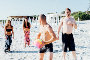 Group of friends millennials playing on the beach with beach ball - activiies, sportive, having fun concept