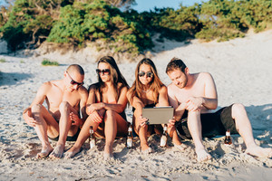 Group of friends millennials sitting on the beach using tablet - social addicted, phubbing, technology concept