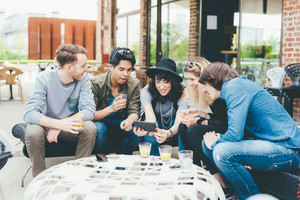 Group of friends millennials sitting outdoor in a bar using smart phone, having fun - interaction, togetherness, socializing concept