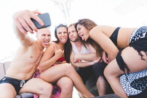 Group of friends millennials using smart phone taking selfie - social network, friendship, having fun concept