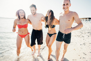 Group of friends millennials walking arm around on the seashore having fun - friendship, interaction, happiness concept