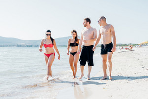 Group of friends millennials walking on the seashore having fun - friendship, interaction, happiness concept