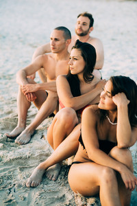 Group of friends millennials wearing swimsuits sitting on the beach on the beach looking at view - togetherness, friendship concept