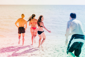 Group of friends millennials wearing swimsuits splashing around - happiness, interaction, togetherness concept