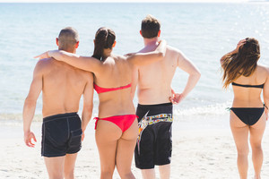 Group of friends millennials wearing swimsuits standing arm around on the beach looking at view - togetherness, friendship concept
