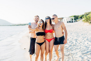 Group of friends millennials wearing swimsuits using smart phone taking selfie - social network, friendship, having fun concept