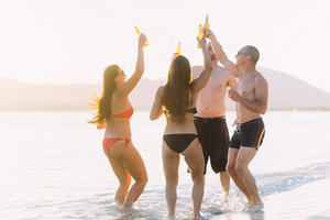 Group of friends on the seashore holding beers, having fun cheering - interaction, friendship, relaxation concept