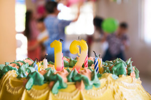 Group of happy children celebrating birthday at home, kids and friends having fun at party. Close-up of cake with candles, and people celebrating in the background.