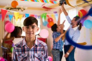 Group of happy children celebrating birthday at home, kids and friends having fun at party. Portrait of happy latino boy smiling, hispanic child looking at camera.