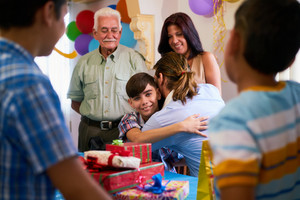 Group of happy children celebrating birthday at home, kids having fun at party. Boy opens present and hugs his father looking at camera.