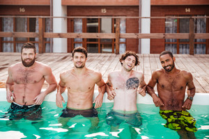 Group of happy confident young men standing in swimming pool