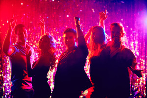 Group of happy friends dancing at party in the night club