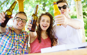 Group of happy friends drinking and having fun in pub garden