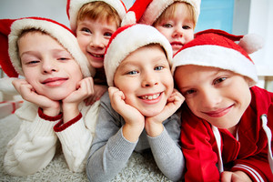Group of happy kids in Santa caps looking at camera