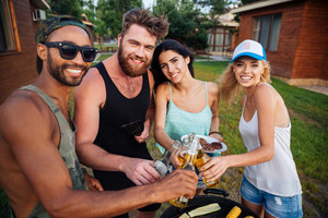 Group of happy smiling friends drinking beer and having barbecue outdoors
