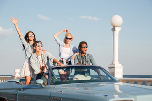 Group of happy young people driving in cabriolet
