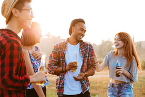 Group of happy young people laughing and drinking beer and soda outdoors