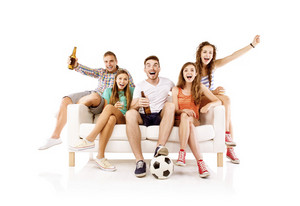 Group of happy young people sitting on sofa and holding soccer ball and bottled drinks, isolated on white background. Best friends