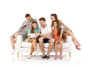 Group of happy young people sitting on sofa and using digital tablet, isolated on white background. Best friends
