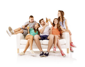Group of happy young people sitting on sofa with bottled drinks, isolated on white background. Best friends