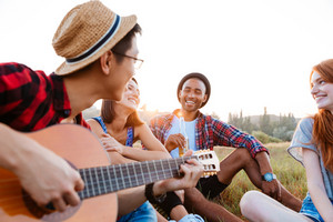 Group of happy young people sitting outdoors and playing guitar together