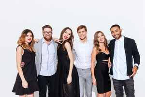 Group of happy young people standing together over white background