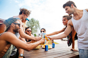 Group of happy young people with beer celebrating together outdoors