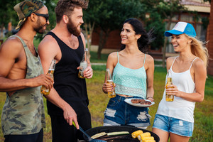 Group of happy young people with beer standing and frying vegetables on barbeque grill outdoors
