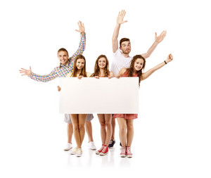 Group of happy young teenager students standing and smiling with blank placard board isolated on white background.