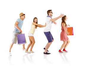 Group of happy young teenager students standing and smiling with shopping bags isolated on white background.