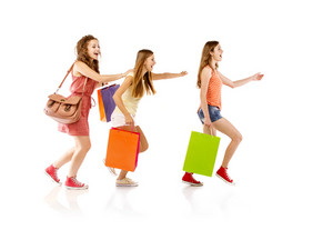 Group of happy young teenager students women standing and smiling with shopping bags isolated on white background.