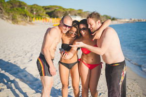 Group of multiethnic friends interacting with technological devices on the beach at sunset - group of friends using a smartphone and taking a selfie on the beach in summertime