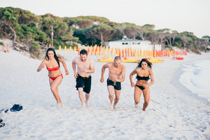 Group of multiethnic man and woman friends in summertime running on the beach, smiling - friendship, summer, joyful concept