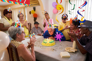 Group of old friends and family celebrating senior man 80 birthday party in retirement home. Happy elderly people having fun. Grandfather blowing candles on cake.