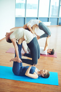 Group of people doing exercise for balance on mats in gym