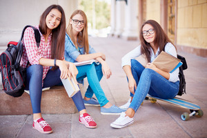 Group of pretty students looking at camera in urban environment