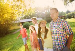 Group of six teenage friends having fun in park