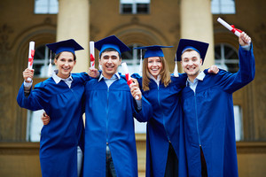 Group of smart students in graduation gowns holding diplomas