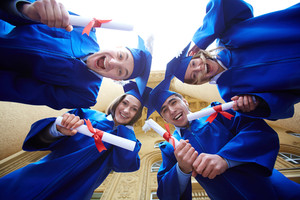 Group of smart students in graduation gowns looking at camera