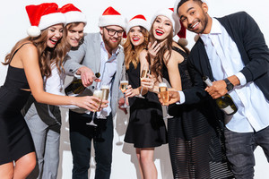 Group of smiling joyful young people in santa claus hats drinking champagne together over white background