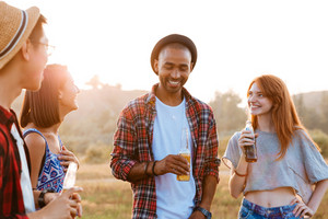 Group of smiling young friends standing and talking outdoors