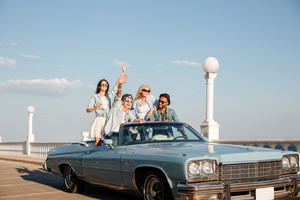 Group of smiling young people driving old vintage cabriolet car