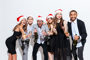 Group of smiling young people in santa claus hats drinking champagne over white background