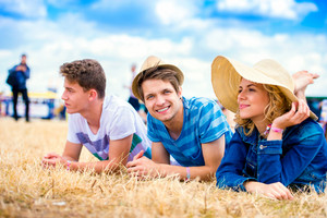 Group of teenage boys and girl at summer music festival, lying on the ground