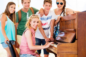 Group of teenage boys and girls at summer music festival, beautiful young woman plays the piano. Sunny day.