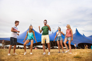 Group of teenage boys and girls at summer music festival, dancing in front of big tent, sunny day