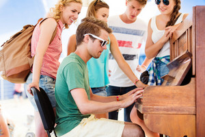 Group of teenage boys and girls at summer music festival, handsome young man plays the piano. Sunny day.