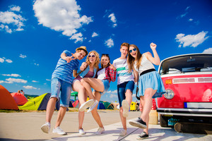 Group of teenage boys and girls at summer music festival posing by vintage red campervan