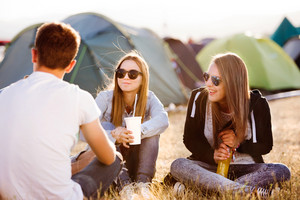 Group of teenage boys and girls at summer music festival, sitting on the ground in front of tents eating and drinking